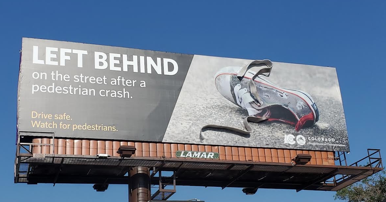 """Billboard photo of shoe with message """"left behind on the street after a pedestrian crash. Drive Safe Watch for Pedestrians."""""""