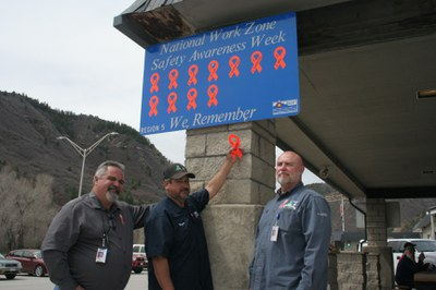 CDOT Region 5, Section 3 employees (l-r) Greg Stacy, Maintenance Superintendent; Myron Olguin, Traffic Unit; and John Palmer, Deputy Maintenance Superintendent get ready to place a ribbon plaque on a memorial sign honoring David D. Morris. Mr. Morris, a CDOT employee, died in the line of duty last spring when a semi-truck collided with his truck in a work zone on US 50 Monarch Pass. Courtesy, Lisa Schwantes, CDOT Region 5 Communications Manager